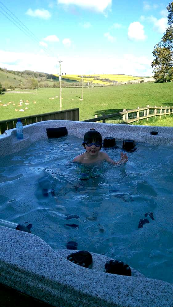 Child in an Arctic Spas Hot tub in the garden