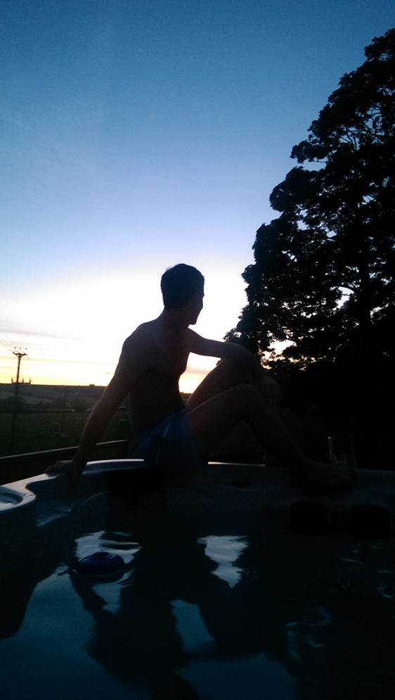 A man next to the hot tub overlook sunset