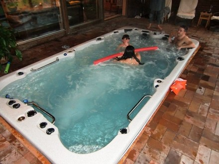 Family having fun in an arctic spas swim spa inside a house