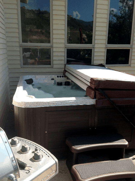 Half covered arctic spas hot tub on a patio